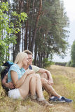 Romantic hiking couple looking away while relaxing in forest Stock Image