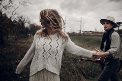 Romantic hipster couple, handsome musician man with guitar and g Stock Images
