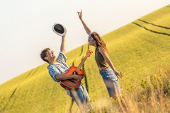 Young couple in love playing guitar and dancing in the field. Romantic hipster couple singing their favorite song in nature. Love and summertime concept stock image