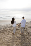 Romantic Hispanic couple watching sunrise at beach Stock Photo