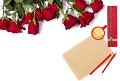 Romantic holiday mockup. Beautiful bunch of large red roses, sheet of craft paper, color pencils, small cup of coffee and present Stock Photo