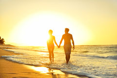 Romantic honeymoon couple in love at beach sunset. Honeymoon romantic couple in love holding hands walking on beautiful sunset at beach in waterfront. Lovers or Royalty Free Stock Images