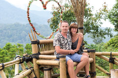 A romantic honeymoon couple on the wooden chair in the mountains of tropical Bali island, Indonesia. Royalty Free Stock Photos