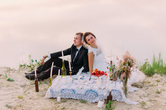 The romantic horizontal portrait of the newlyweds sirring back-to-back while having the wedding picnic on the coast the Stock Photos