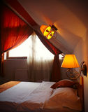 Romantic hotel room. Romantic interior in a hotel room with red curtains and elegant lamps stock photography