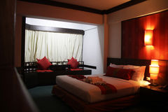 Romantic hotel room;. Romantic hotel room. One big bed with white and red pikkows. The lamb on the ctand near the bed. Two seat with red pillows behind the bed stock images