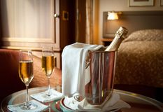 Luxury hotel room with champagne. Romantic hotel room setting with champagne in a bucket and two glasses royalty free stock image