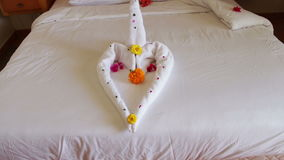 Romantic Hotel Room with Swan Towels. White towel on the bed in a hotel room in the shape of a heart or a swan with flowers and petals stock video footage