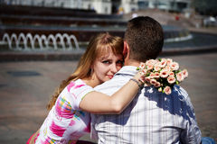 Romantic hug the guy and girl. On branch in city park Stock Image