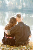 Romantic hug. Young male and female sitting near water he giving her hug rear view Royalty Free Stock Image