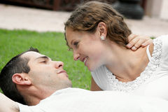 Romantic image of beautiful couple smiling at each. Other laying on the grass in the park Royalty Free Stock Photos