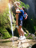 Romantic image, man lifted up woman beside forest waterfall royalty free stock images