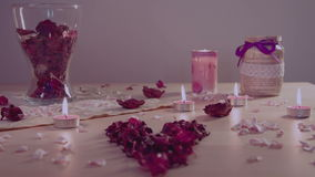 Romantic installation on a table: burning candles, heart-shaped flowers, pot pourri. Soft zoom out and changing focus stock footage