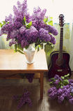 Romantic interior design with lilac flowers and red guitar Stock Photos