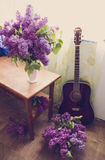 Romantic interior design with lilac flowers and red guitar in warm tones Royalty Free Stock Photos