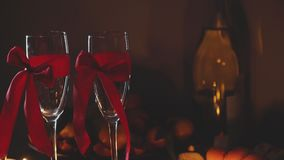 Romantic Interior: dim lights, candles, two glasses of champagne. Slowmotion. Romantic Interior: dim lights, candles, two glasses of champagne with red ribbon stock video footage