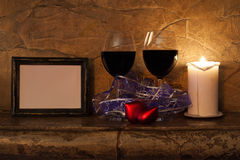 Romantic interior. glasses of wine, candles, hearts and photo frame Stock Images
