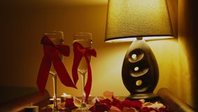 Romantic Interior: two glasses with red ribbon, rose petals on the bed stock video footage