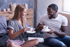 Romantic international couple enjoying weekend at home. Happiness around us. Positive delighted international couple sitting in the bedroom and drinking tea Royalty Free Stock Photo