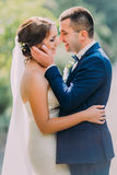 Romantic just married couple holding each other outdoor at sunny day Stock Image
