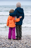 Happy siblings kids on beach winter back Royalty Free Stock Photography