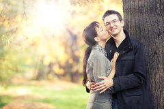 Romantic kiss. Pretty young girl kisses in cheeck her boyfriend in the park; autumn leaves and sunbeams on the background; there is a heart carved on the tree Stock Photo