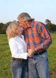 Romantic Kiss. A good looking mature couple kissing in the late afternoon sun Stock Images