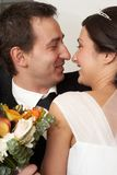 Romantic kiss. Groom embracing his bride in the beginning of the wedding day stock photo