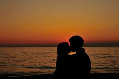 Romantic kiss on beach at the sunset time. Kissing couple on the beach with little peace of sun royalty free stock photography