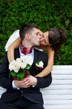 Romantic kiss beloved bride and groom. On wedding walk Stock Photography