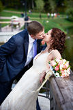Romantic kiss bride and groom. On wedding walk Stock Photo