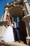 Romantic kiss bride and groom and ancient building. Romantic kiss bride and groom at wedding walk near ancient brick building Royalty Free Stock Photography