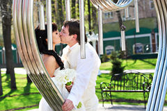 Romantic kiss bride and groom about art ironwork. On wedding walk Stock Photos