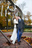 Romantic kiss bride and groom in autumn park. Romantic kiss bride and groom about iron figure on autumn wedding walk Stock Photos