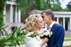 Romantic kiss bride and groom on wedding walk. In park Stock Photos