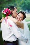 Romantic kiss happy bride and groom. On wedding walk Stock Images