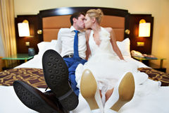 Romantic kiss happy bride and groom in bedroom. On wedding day Stock Images
