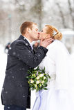 Romantic kiss happy bride and groom on winter Stock Images