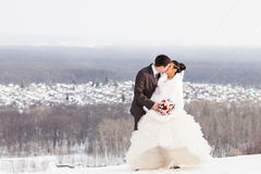 Romantic kiss happy bride and groom on winter wedding day Stock Photography