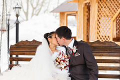 Romantic kiss happy bride and groom on winter wedding day Stock Images