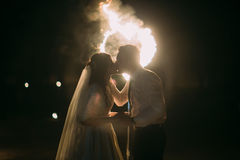 Romantic kiss just married couple in front of flaming heart. Night shot Royalty Free Stock Images