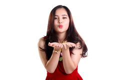 Romantic kiss of lady in red. Lovely young Asian lady in red dress blowing romantic kiss to camera, isolated on white background Royalty Free Stock Photography