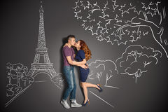 Romantic kiss in Paris. Happy valentines love story concept of a romantic couple in Paris kissing under the Eiffel Tower against chalk drawings background Stock Image