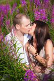 Romantic kiss among purple flowers Royalty Free Stock Photos