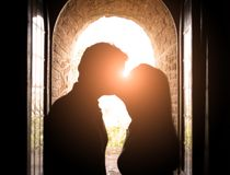 Romantic kiss at sunset. Couple kissing at sunset and window in the background royalty free stock image