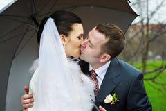 Romantic kiss at wedding walk. Romantic kiss bride and groom at the wedding walk with umbrella Royalty Free Stock Image
