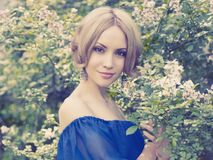 Romantic lady in the garden. Portrait of beautiful romantic lady in the flowered garden Stock Images