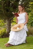 Romantic lady reading  a book sitting Stock Photos