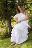 Romantic lady reading  a book sitting Stock Images