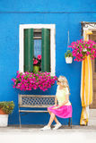 Romantic lady sitting on bench in front of house Royalty Free Stock Photography